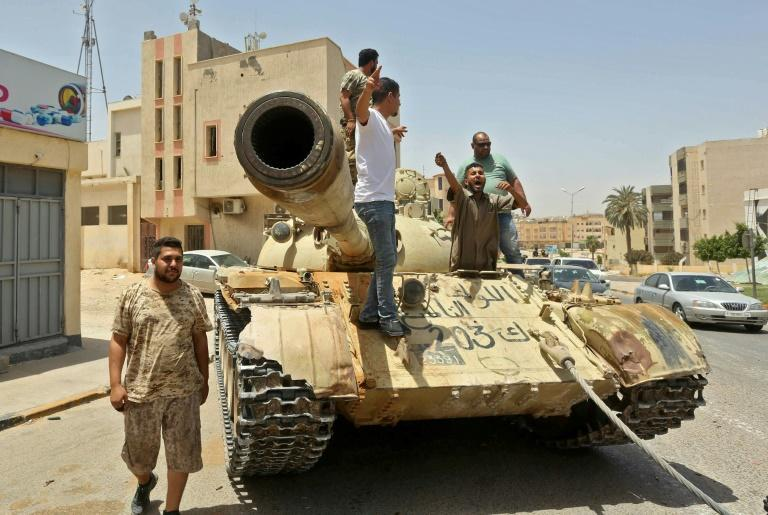Fighters loyal to Libya's UN-recognised Government of National Accord (pictured June 2020) stand on a tank in the town of Tarhuna, after the area was taken over by pro-GNA forces from rival forces loyal to strongman Khalifa Haftar