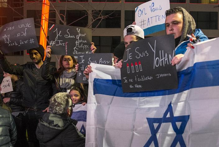 French-Israeli dual nationals hold signs during a remembrance ceremony for the victims of the Charlie Hebdo attack in France, in Netanya, Israel, on January 11, 2015 (AFP Photo/Jack Guez)