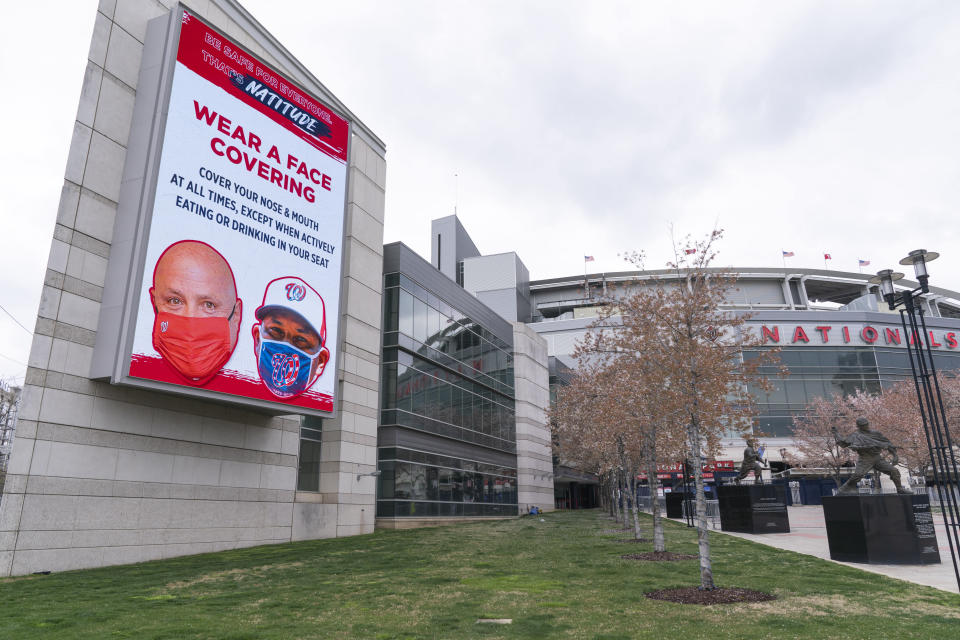 An electronic sign encouraging mask wearing is seen at Nationals Stadium, after the opening day baseball game between the Washington Nationals and New York Mets was postponed because of coronavirus concerns, Thursday, April 1, 2021, in Washington. The entire season-opening three-game series between the Washington Nationals and New York Mets was called off on Friday after three players for the 2019 World Series champions tested positive for COVID-19.(AP Photo/Jacquelyn Martin)