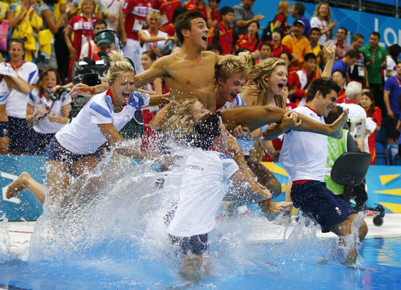 Britain's Tom Daley (C) is thrown into the pool by the British diving team after he won the bronze medal in the men's 10m platform final at the London 2012 Olympic Games at the Aquatics Centre August 11, 2012.    REUTERS/Michael Dalder (BRITAIN  - Tags: SPORT DIVING OLYMPICS TPX IMAGES OF THE DAY)