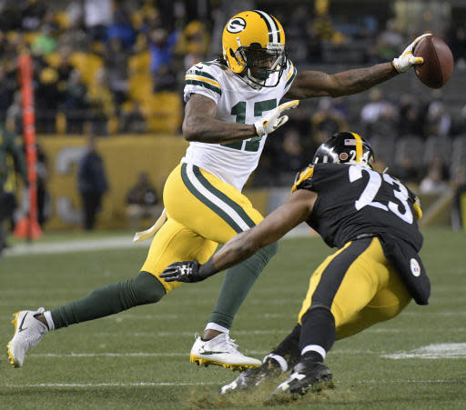 FILE - In this Sunday, Nov. 26, 2017 file photo, Green Bay Packers wide receiver Davante Adams (17) eludes the tackle by Pittsburgh Steelers free safety Mike Mitchell (23) and heads for the end zone after taking a pass from quarterback Brett Hundley during the second half of an NFL football game in Pittsburgh. The Green Bay Packers opened on-field work in their offseason program this week, an especially important time for a team that has had a lot of changes since the end of a 7-9 season (AP Photo/Don Wright, File)