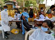 FILE PHOTO: A healthcare worker collects a swab sample from a man during a rapid antigen testing campaign for the coronavirus disease (COVID-19), in Mumbai