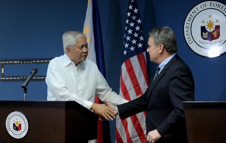 Philippines Foreign Secretary Albert del Rosario (L) shakes hands with US Congressman Chris Smith during a joint press conference in Manila on November 25, 2013