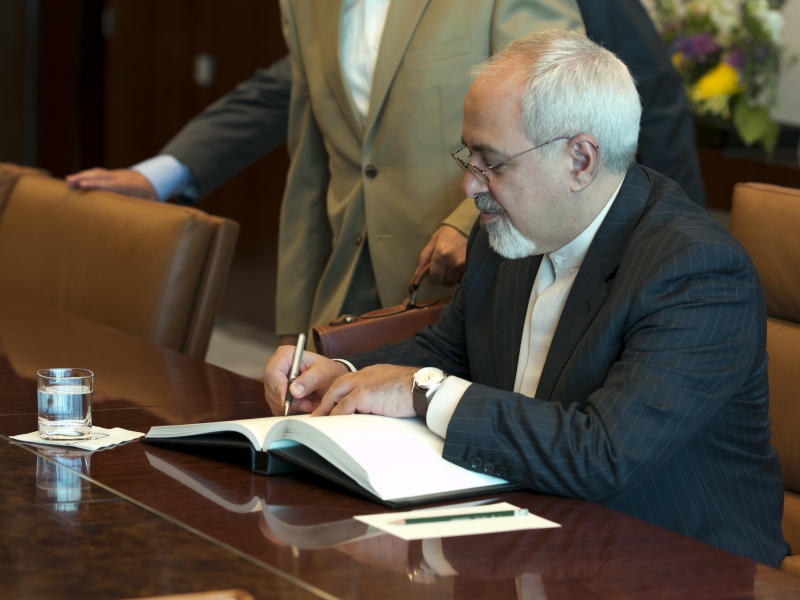 Iran's Foreign Minister Javad Zarif signs the guest book in the office of U.N. Secretary General Ban Ki-moon, at United Nations headquarters, Thursday, Sept. 19, 2013. (AP Photo/Richard Drew)