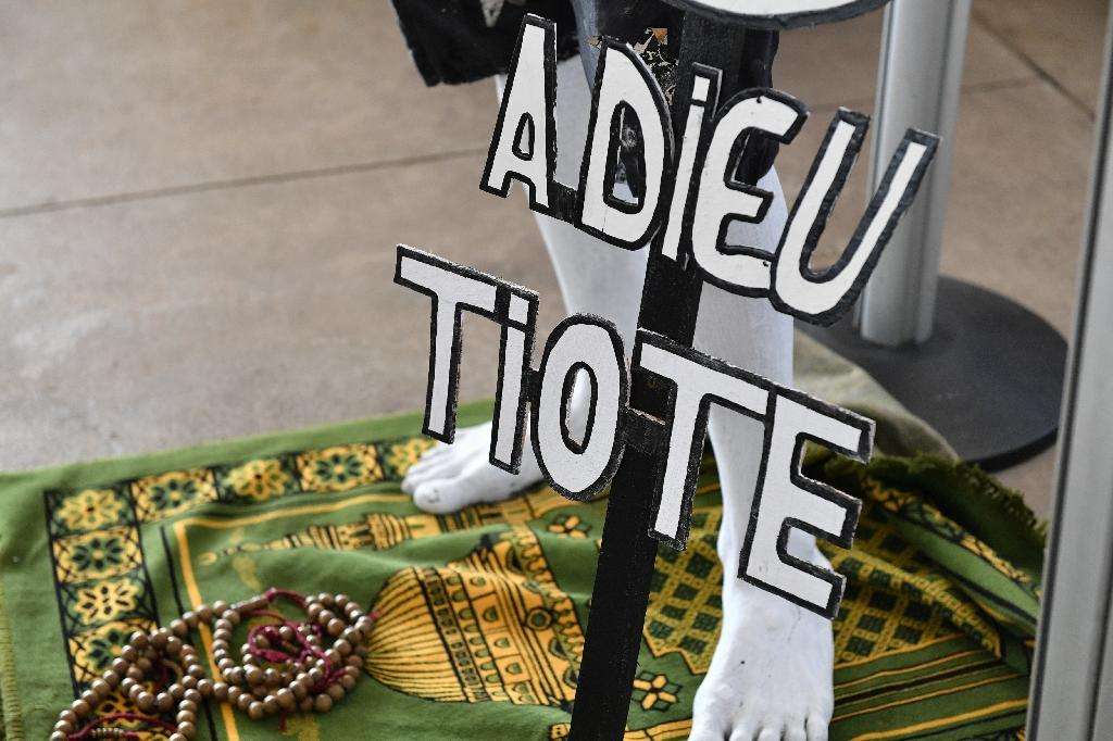"A supporter holding a sign reading ""Farewell Tiote"" attends the arrival of the casket of the late Ivory Coast midfielder Cheick Tiote, on June 15, 2017 upon its arrival from China at Abidjan's airport, prior to his funeral ceremony (AFP Photo/ISSOUF SANOGO)"