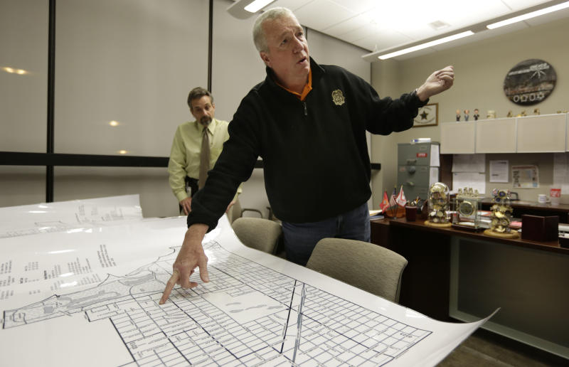 In this Dec. 11, 2012 file photo, Jack Riley, head of the Drug Enforcement Administration in Chicago, points out local Mexican drug cartel problem areas on a map in the new interagency Strike Force office in Chicago. Looking on is DEA agent Vince Balbo. The ruthless syndicates have long been the nation's No. 1 supplier of illegal drugs, but in the past, their operatives rarely ventured beyond the border. A wide-ranging Associated Press review of federal court cases and government drug-enforcement data, plus interviews with many top law enforcement officials, indicate the groups have begun deploying agents from their inner circles to the U.S. (AP Photo/M. Spencer Green, File)