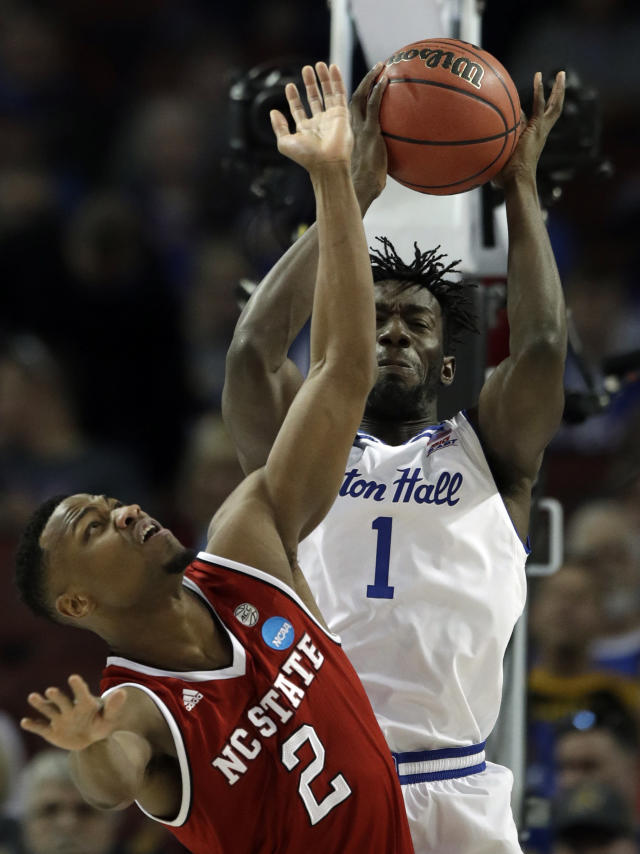 Seton Hall forward Michael Nzei (1) rebounds over North Carolina State guard Torin Dorn (2) during the first half of an NCAA college basketball tournament first-round game, Thursday, March 15, 2018, in Wichita, Kan. (AP Photo/Orlin Wagner)