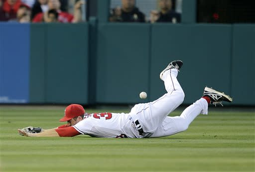 Los Angeles Angels left fielder J.B. Shuck misses a ball hit for a double by Minnesota Twins' Aaron Hicks during the second inning of a baseball game on Monday, July 22, 2013, in Anaheim, Calif. (AP Photo/Jae C. Hong)
