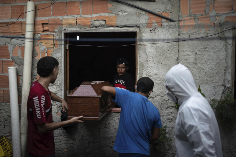 Relatives help a SOS Funeral worker, wearing protection equipment amid the new coronavirus outbreak, remove the body of Eldon Cascais from his home in Manaus, Brazil, Saturday, May 9, 2020. According to Cascais' relatives, he had lung cancer and died at home after suffering from shortness of breath, cough and fatigue for a week. (AP Photo/Felipe Dana)