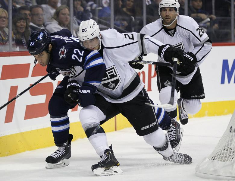 Winnipeg Jets' Chris Thorburn (22) and Los Angeles Kings' Slava Voynov (26) drive for the puck as Kings' Jarret Stoll watches during the second period of an NHL hockey game in Winnipeg, Manitoba, on Friday, Oct. 4, 2013. (AP Photo/The Canadian Press, John Woods)