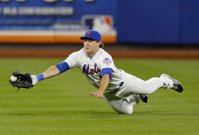 New York Mets center fielder Matt den Dekker (6) makes a diving catch on a short hop hit by Milwaukee Brewers' Jeff Bianchi for an RBI single in the second inning of a baseball game at Citi Field in New York, Thursday, Sept. 26, 2013. (AP Photo/Paul J. Bereswill)
