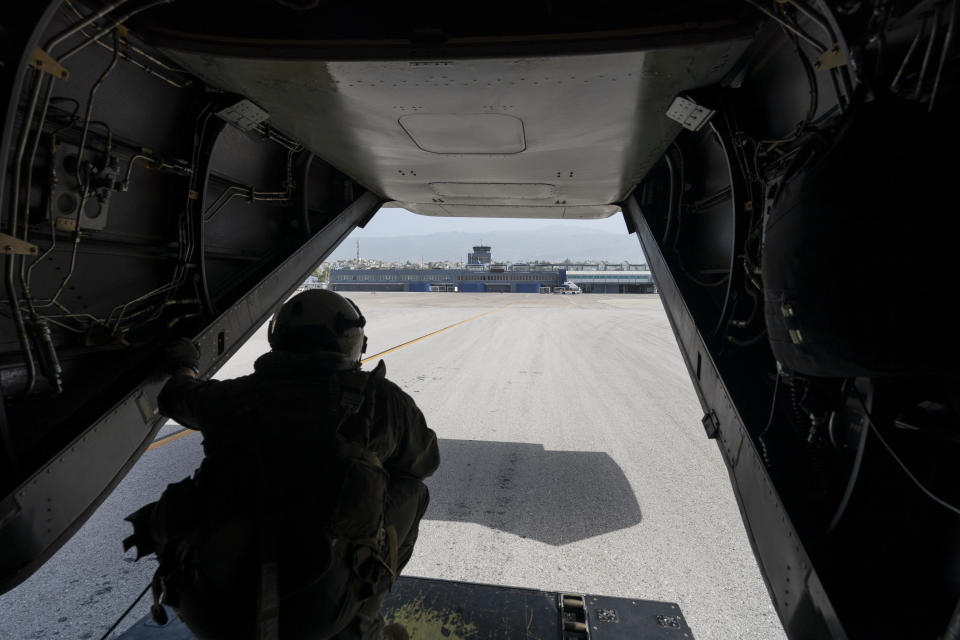 """U.S. Marine Cpl. Thalles Souza, watches as a VM-22 Osprey, loaded with relief aid, taxis for departure at Toussaint Louverture International Airport, Saturday, Aug. 28, 2021, in Port-au-Prince, Haiti. The VMM-266, """"Fighting Griffins,"""" from Marine Corps Air Station New River, from Jacksonville, N.C., are flying in support of Joint Task Force Haiti after a 7.2 magnitude earthquake on Aug. 22, caused heavy damage to the country. (AP Photo/Alex Brandon)"""