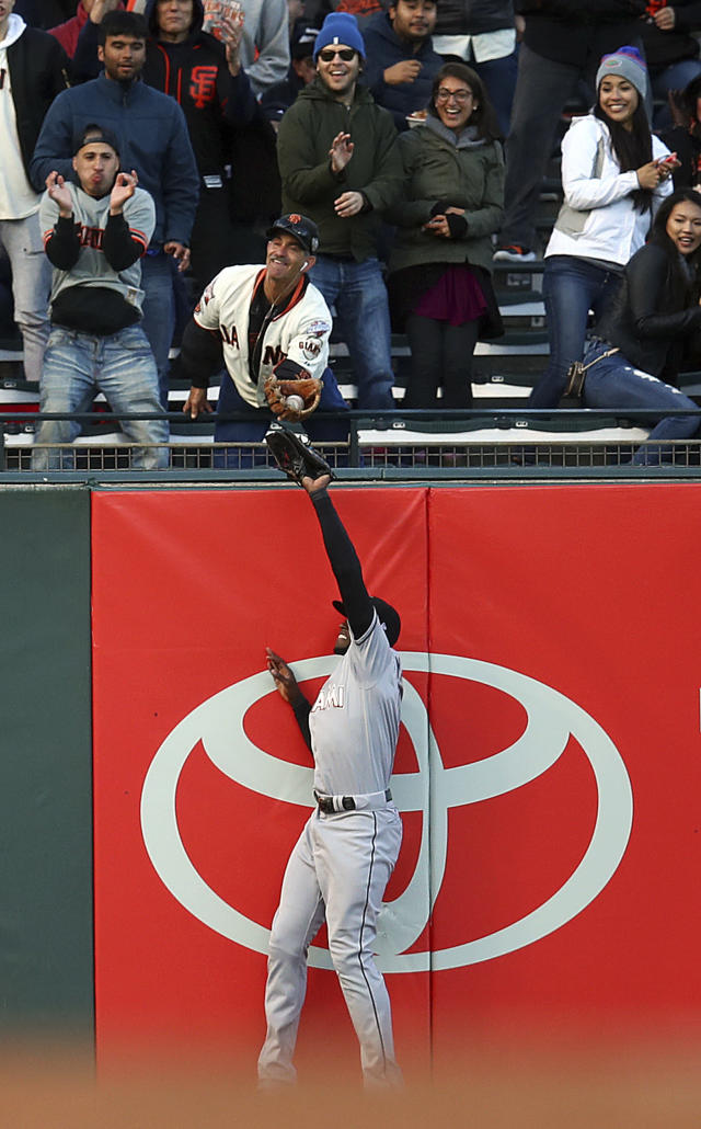 A fan catches a two-run home run hit by San Francisco Giants' Pablo Sandoval over Miami Marlins left fielder Cameron Maybin in the second inning of a baseball game Monday, June 18, 2018, in San Francisco. (AP Photo/Ben Margot)