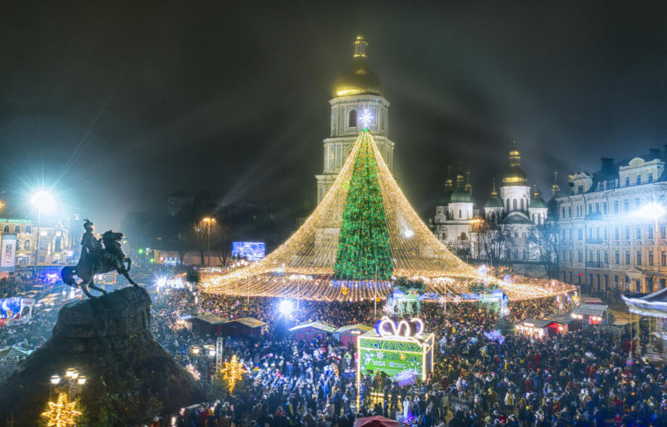 Crowds of people celebrate the New Year around the Christmas tree with the St. Sofia Cathedral in the background in Kyiv, Ukraine, early Friday, Jan. 1, 2021. Despite of COVID-19 quarantine restrictions, a lot of Ukrainians enjoy outdoor New Year events, often ignoring protective measures. (AP Photo/Efrem Lukatsky)