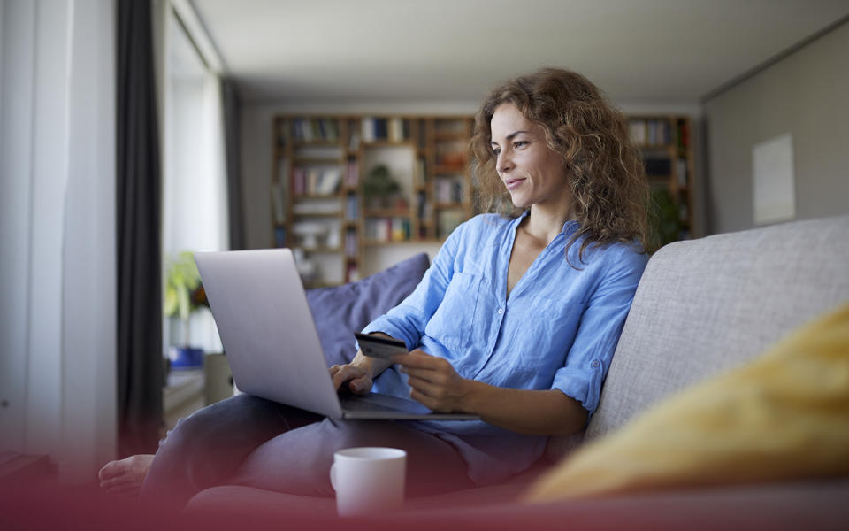 Woman sits in front of computer online shopping.
