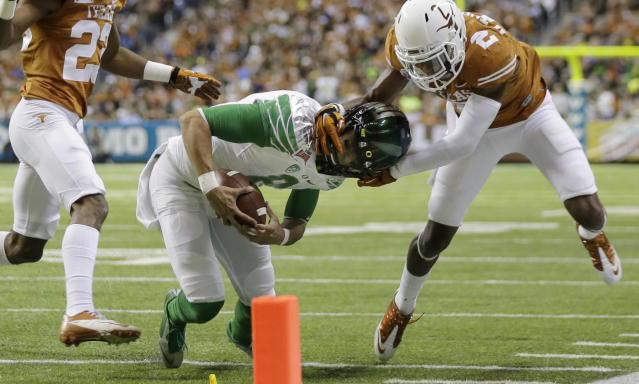 Oregon's Marcus Mariota (8) is pulled down by his helmet by Texas' Mykkele Thompson (2) during the first quarter in the Valero Alamo Bowl NCAA college football game, Monday, Dec. 30, 2013, in San Antonio. (AP Photo/Eric Gay)