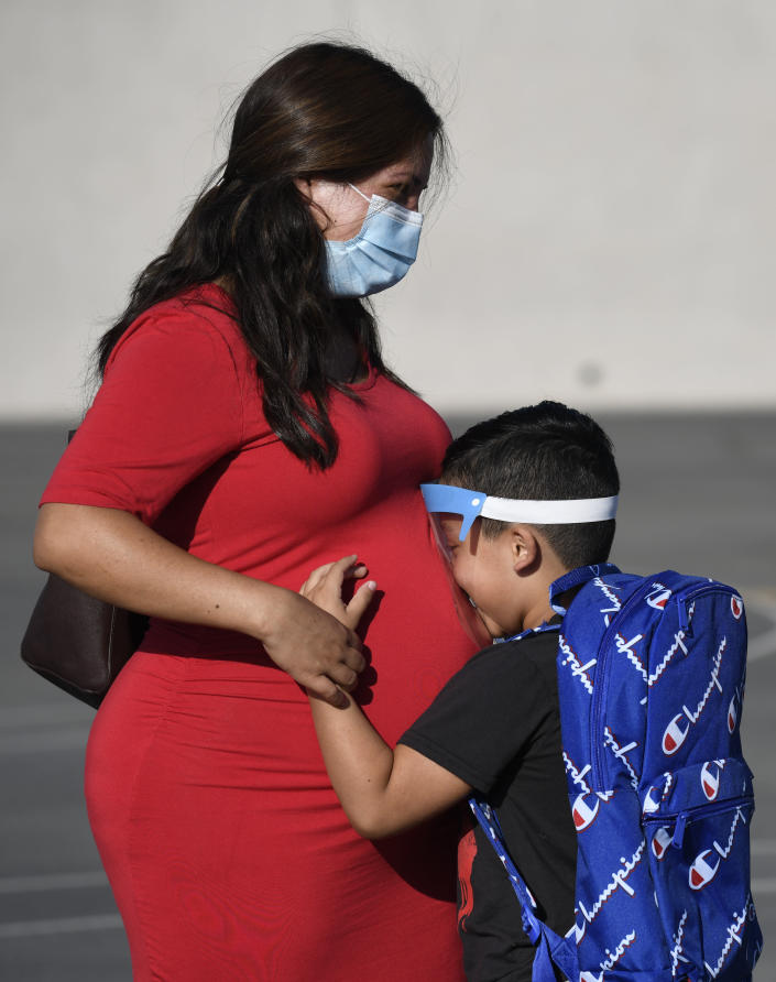 A student wearing a visor hugs his mother on the first day of school at Enrique S. Camarena Elementary School, Wednesday, July 21, 2021, in Chula Vista, Calif. The school is among the first in the state to start the 2021-22 school year with full-day, in-person learning. (AP Photo/Denis Poroy)