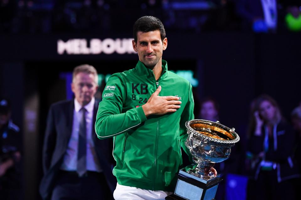 Serbia's Novak Djokovic smiles and thanks the crowd with the Norman Brooks Challenge Cup trophy.