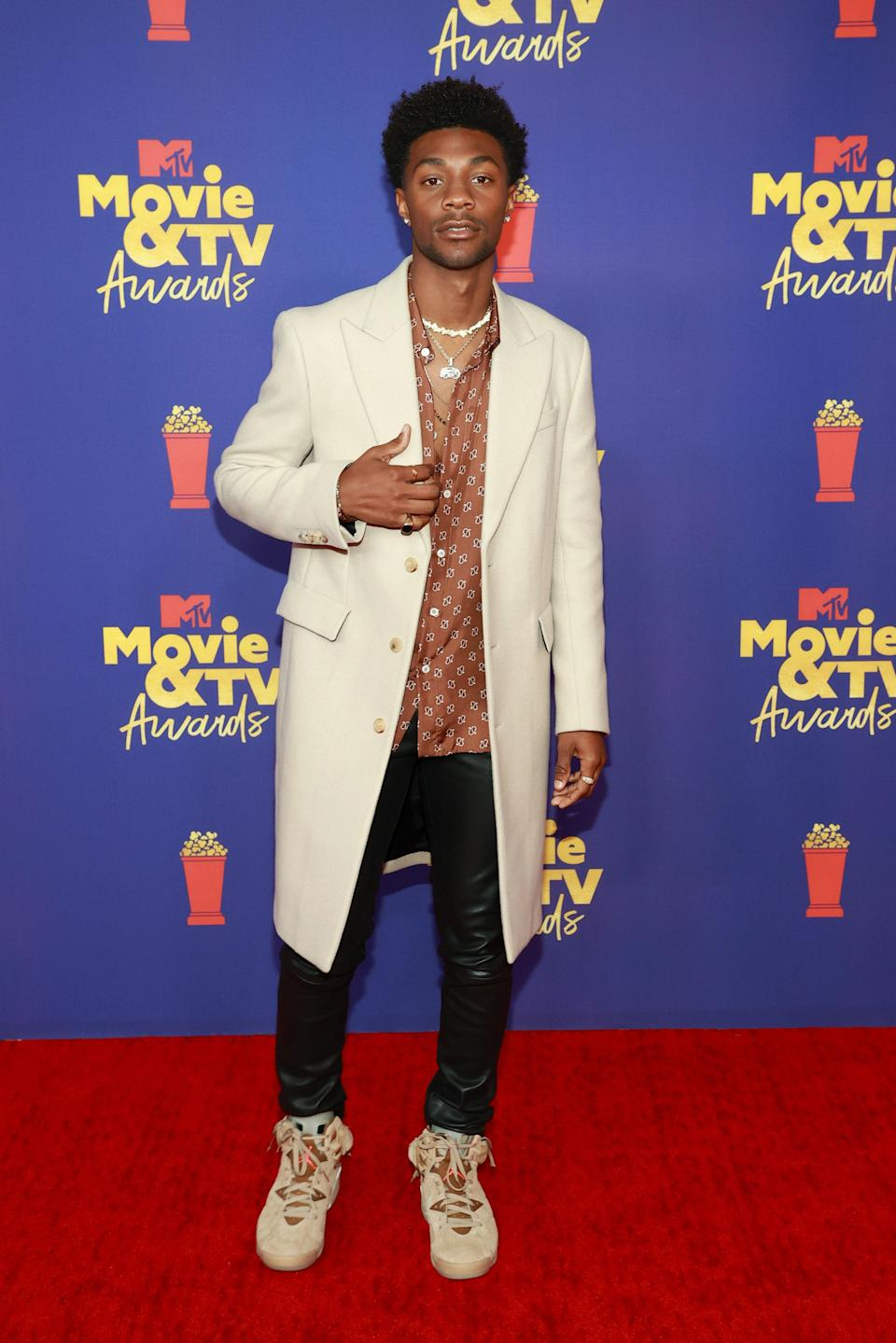 Johnathan Daviss looked sharp as ever in his tonal red carpet look. The <em>Outer Banks</em> star wore a cream coat, a satin brown shirt, black leather skinnies, and a sand pair of Jordans.