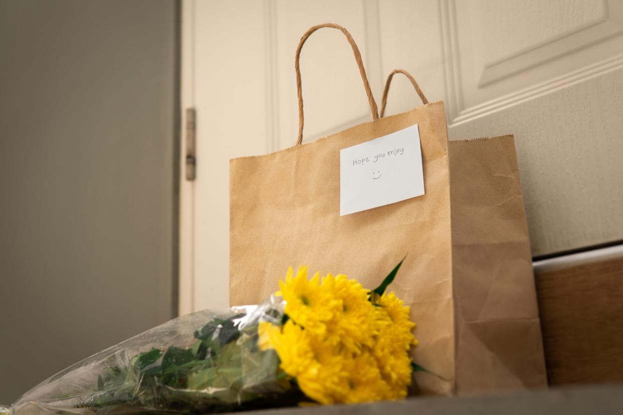 Delivery yellow chrysanthemums bouquet and reusable paper bag with card at home entrance white door in a daytime