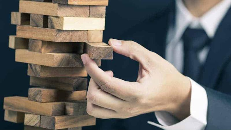 Businessman pulling out wooden brick from toppling stack