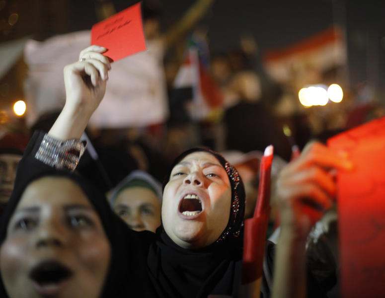 """Egyptian protesters flash red cards with Arabic that reads """"Leave"""" and shout slogans against Egyptian President Mohammed Morsi as they watch his speech at Tahrir Square, the focal point of Egyptian uprising, in Cairo, Egypt, Wednesday, June 26, 2013. In abstract terms, protests planned for Sunday, June 30 aiming to force out Egypt's Islamist president violate a basic principle of democracy: If an election has been held, all must respect the results, otherwise it?s political chaos. Supporters of President Mohammed Morsi have been angrily making that argument for days. Those behind the protests insist he lost the legitimacy of that election victory by power grabs and missteps. (AP Photo/Amr Nabil)"""