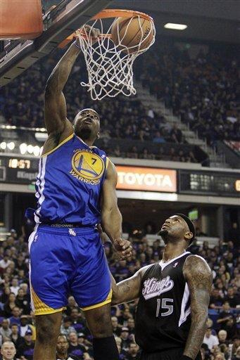 Golden State Warriors forward Carl Landry, left, dunks over Sacramento Kings center DeMarcus Cousins during the first half of an NBA basketball game in Sacramento, Calif., Monday, Nov. 5, 2012. (AP Photo/Rich Pedroncelli)