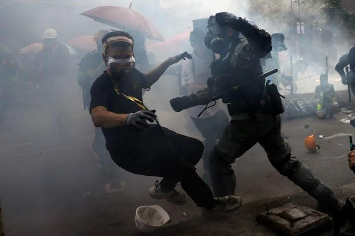 A protester is detained by riot police while attempting to leave the campus of Hong Kong Polytechnic University (PolyU) during clashes with police in Hong Kong