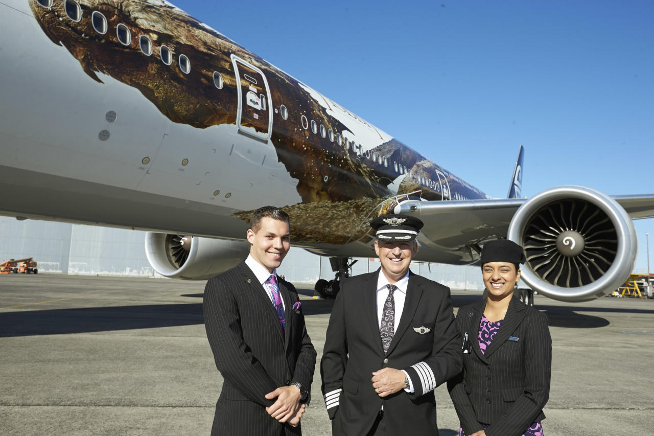 """In this photo released by Air New Zealand, Air New Zealand crew members Maxence Cherri, left, Priyanka Girish, right, and captain David Morgan, center, stand in front of a plane with an image of the dragon Smaug from Peter Jackson's Hobbit trilogy, on Monday, Dec. 2, 2013, in Auckland, New Zealand. The image was unveiled to celebrate the premiere of """"The Hobbit: The Desolation of Smaug,"""" which screens Monday in Los Angeles. (AP Photo/Air New Zealand)"""