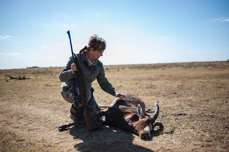 Adri Kitshoff, chief executive officer of Professional Hunters' Association of South Africa (PHASA), kneels by an antelope she hunted at the Iwamanzi Game Reserve in Koster on June 6, 2015 (AFP Photo/Stefan Heunis)