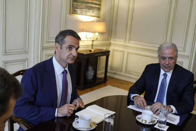 Greece's Prime Minister Kyriakos Mitsotakis, left, looks on next to European Commissioner for Migration and Home Affairs Dimitris Avramopoulos during a meeting about migration policy in Athens, on Monday , July 15, 2019. (AP Photo/Petros Giannakouris)