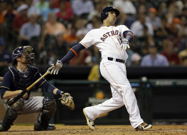 Houston Astros' Carlos Pena, right, hits a three-run home run as Milwaukee Brewers' Jonathan Lucroy, left, watches during the fifth inning of a baseball game Tuesday, June 18, 2013, in Houston. (AP Photo/David J. Phillip)