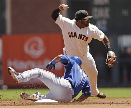 San Francisco Giants third baseman Pablo Sandoval, top, attempts a double play over Texas Rangers' Elvis Andrus on a ground ball by Josh Hamilton during the first inning of a baseball game in San Francisco, Saturday, June 9, 2012. Hamilton was safe at first. (AP Photo/Marcio Jose Sanchez)