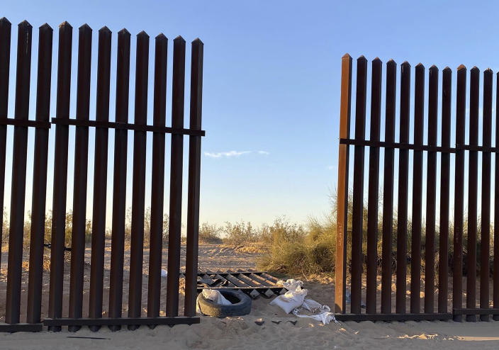 FILE - This file photo provided by U.S. Customs and Border Protection shows a hole cut into Southern California's border fence with Mexico on Wednesday, March 3, 2021. Nine migrants in an SUV packed with 25 people that drove through an opening in a border wall suffered major injuries after their vehicle slammed into a tractor-trailer and killed 13 others inside, the California Highway Patrol said Thursday, March 4, 2021. (U.S. Customs and Border Protection via AP)