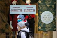 A sign in a German store window invites customers to shop online due to the coronavirus lockdown