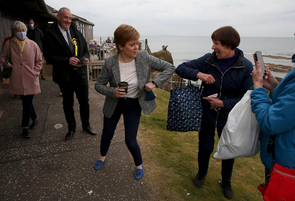 Nicola Sturgeon greets a supporter with an elbow bump on the campaign trail in North Berwick (Andrew Milligan/PA)