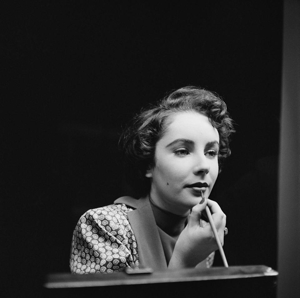 <p>Elizabeth was very skilled at doing her own makeup — and actually preferred doing it herself. Here, the actress is seen putting the final touches on her lips. </p>