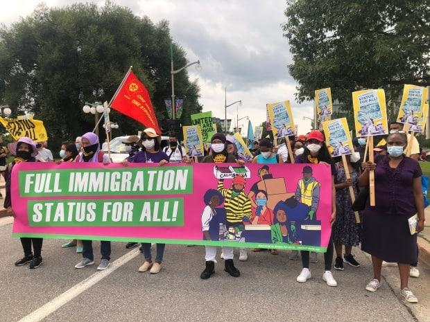 Hundreds of people marched in downtown Ottawa on July 25, 2021 to demand the federal government grant permanent immigration status to all migrants in Canada.  (Krystalle Ramlakhan/CBC - image credit)