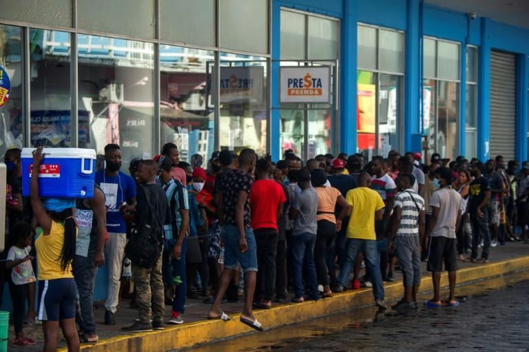 Migrants queue outside banks to collect money sent by relatives in the city of Tapachula in southern Mexico (AFP/CLAUDIO CRUZ)