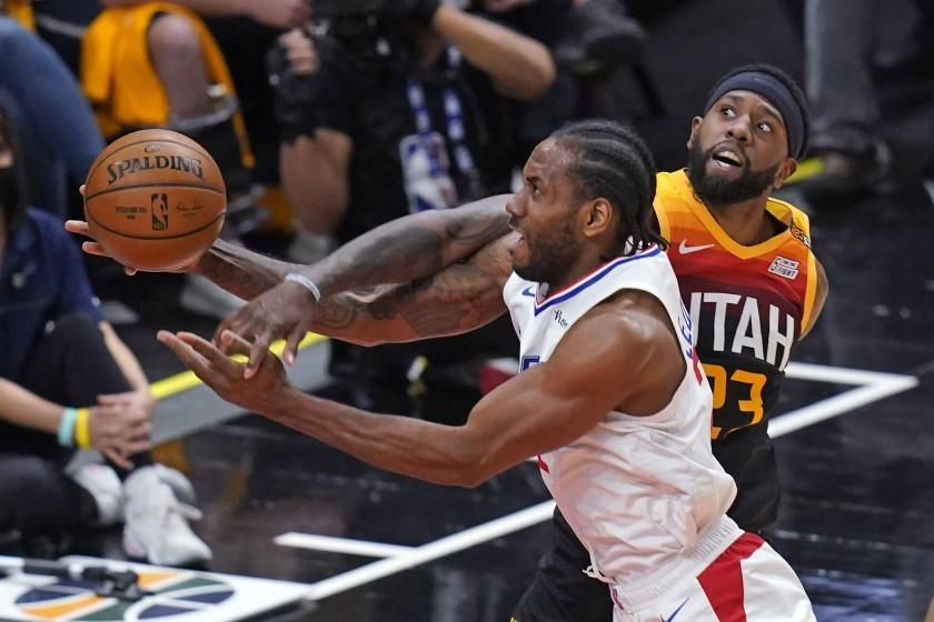 Utah Jazz forward Royce O'Neale, rear, fouls Los Angeles Clippers forward Kawhi Leonard during the first half of Game 1 of a second-round NBA basketball playoff series Tuesday, June 8, 2021, in Salt Lake City. (AP Photo/Rick Bowmer)