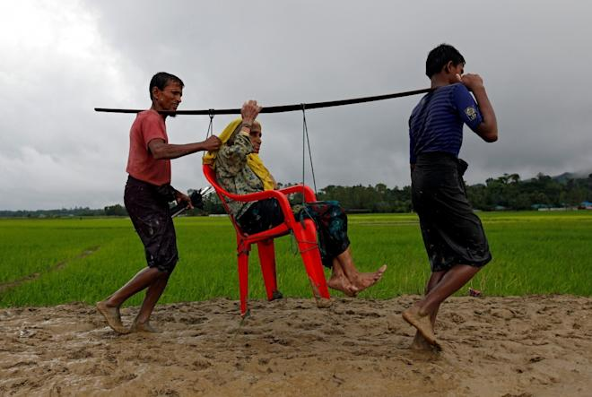 Rohingya refugee men carry an old woman as she is unable to walk after crossing the border, in Teknaf, Bangladesh.