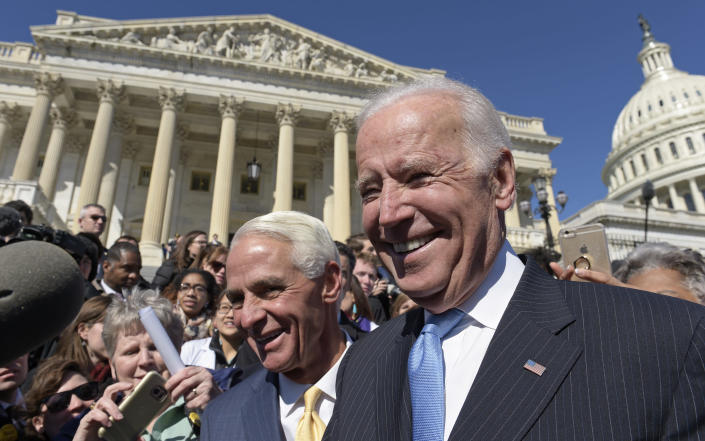 FILE - In this March 22, 2017, file photo former Vice President Joe Biden, right, and Rep. Charlie Crist, D-Fla.,greet the crowd on Capitol Hill in Washington following an event marking seven years since former President Barack Obama signed the Affordable Care Act into law. (AP Photo/Susan Walsh, File)