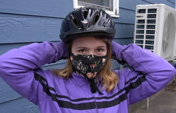 13-year-old Destiny Robichaud-Edison tries on a new helmet.  Each bike comes with one.