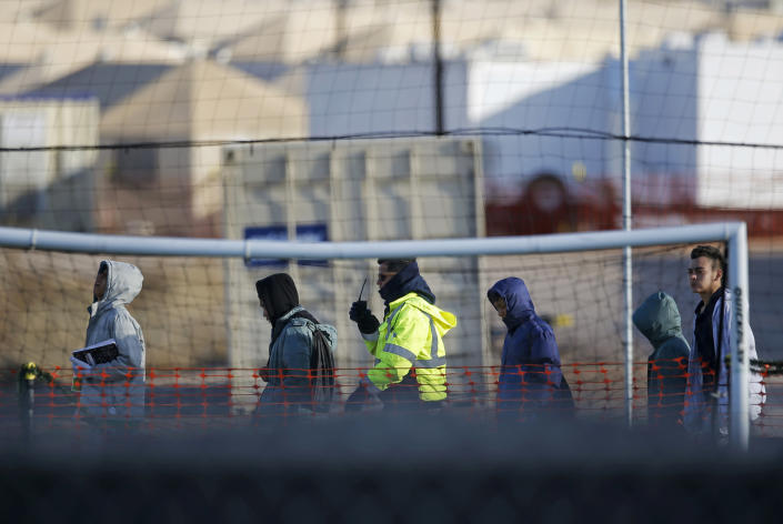 File-In this Dec. 13, 2018, file photo, teen migrants walk in line inside the Tornillo detention camp in Tornillo, Texas. The Biden administration is stepping up its effort to find and unite migrant families forcibly separated under President Donald Trump. (AP Photo/Andres Leighton, File)