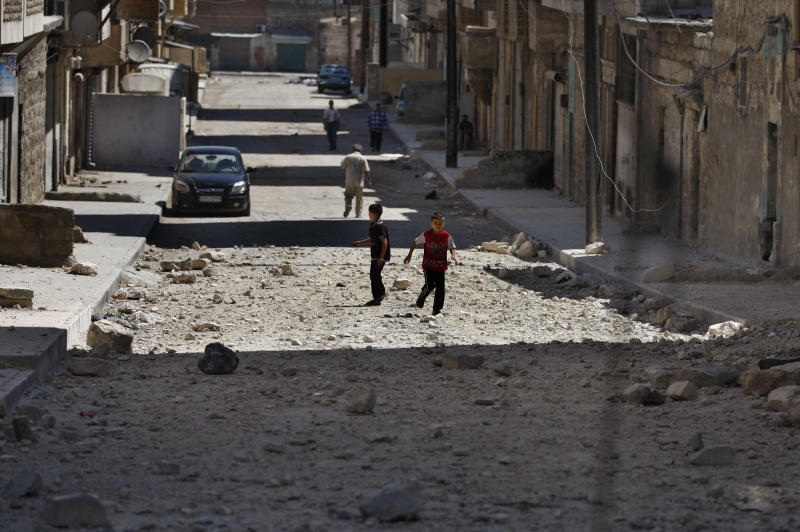 Two Syrian boys play on a street next to a building hit by a Syrian government airstrike in Aleppo, Syria, Sunday, Aug. 19, 2012 (AP Photo/ Khalil Hamra)