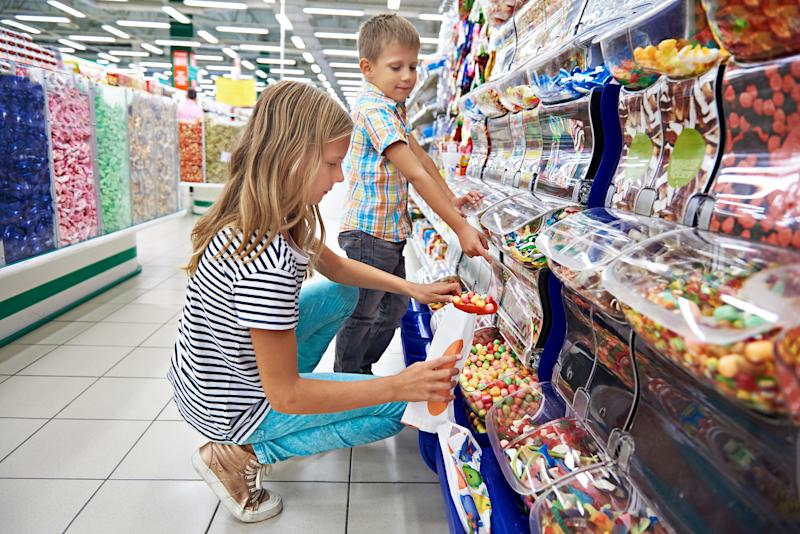 A girl and a boy loading bulk candy into plastic bags at a candy store.