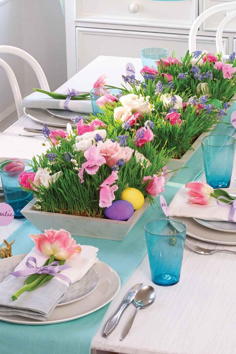 """<p><strong>1.</strong> Arrange medium whitewashed wood trays down the middle of your table. Cut through wheatgrass (available at most nurseries) with scissors so it fits inside each tray.</p><p><strong>2.</strong> Push the stems of cut flowers into floral water picks filled with tap water, then nestle the plastic tubes into the grass.</p><p><strong>3.</strong> For extra color, place a few dyed eggs around the perimeter as shown.</p><p><strong><a class=""""link rapid-noclick-resp"""" href=""""https://www.amazon.com/Floral-Water-Tubes-Florist-Supplies/dp/B073VPC5HL?tag=syn-yahoo-20&ascsubtag=%5Bartid%7C10070.g.1751%5Bsrc%7Cyahoo-us"""" rel=""""nofollow noopener"""" target=""""_blank"""" data-ylk=""""slk:SHOP FLORAL WATER PICKS"""">SHOP FLORAL WATER PICKS</a></strong></p>"""