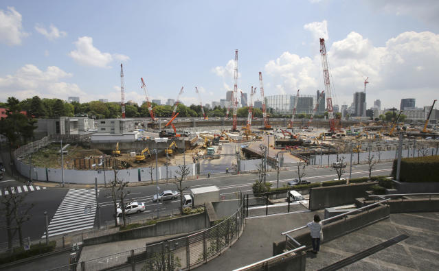 FILE - In this April 28, 2017, file photo, a woman looks at the construction site of the new National Stadium for the 2020 Tokyo Olympics and Paralympics in Tokyo. Tokyo used its famous 1964 Olympics to show off a miraculous recovery from defeat in World War II. This time the Japanese capital will use the games to showcase a clean, safe, and innovative city with great shopping and nightlife. (AP Photo/Koji Sasahara, File)