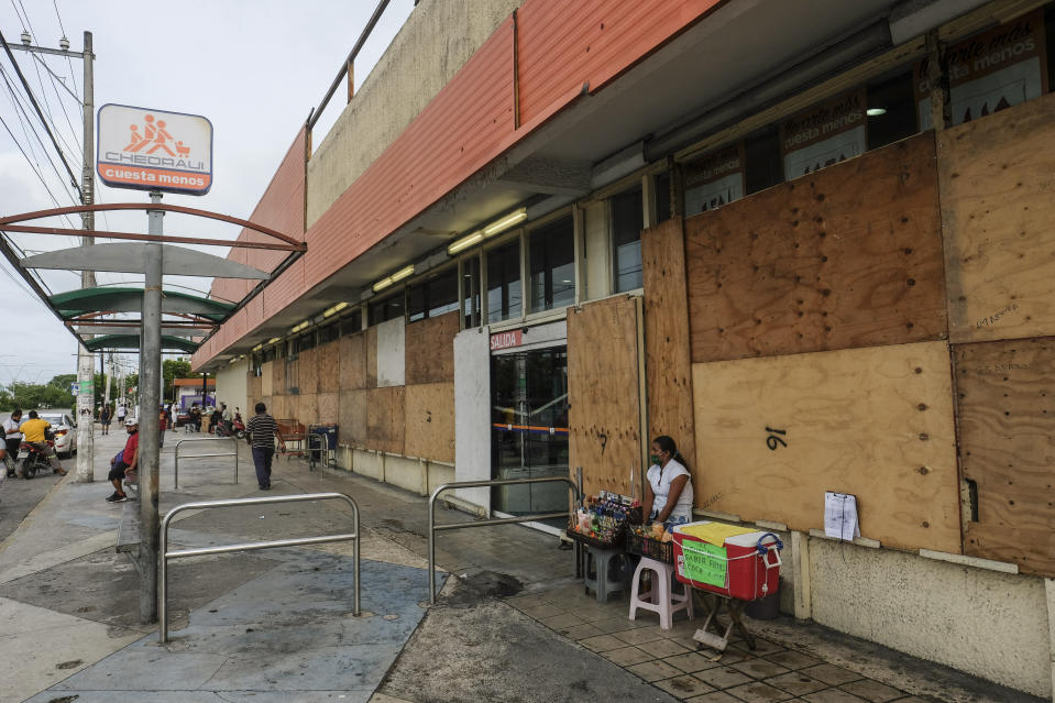 A woman waits for clients outside a supermarket with its windows covered with plywood as Tropical Storm Zeta approaches Cancun, Mexico, Monday, Oct. 26, 2020. A strengthening Tropical Storm Zeta is expected to become a hurricane Monday as it heads toward the eastern end of Mexico's resort-dotted Yucatan Peninsula and then likely move on for a possible landfall on the central U.S. Gulf Coast at midweek. (AP Photo/Victor Ruiz Garcia)
