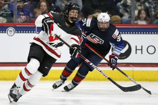 Canada's Rebecca Johnston, left, defends against United States' Kelly Browne (32) during the first period of a rivalry series women's hockey game in Hartford, Conn., Saturday, Dec. 14, 2019. (AP Photo/Michael Dwyer)